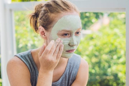 beautiful girl applying facial mask.