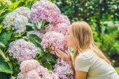 Young woman near Pink hydrangea flowers