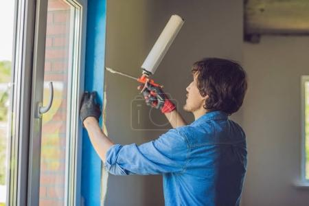 Photo for Man in a blue shirt does window installation. Using a mounting foam. - Royalty Free Image