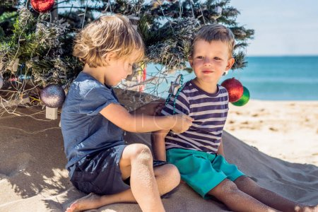 Two boys are celebrating Christmas on the beach.