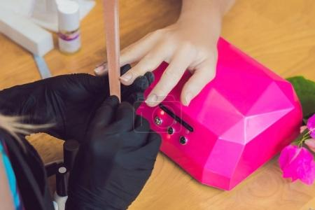 Closeup finger nail care by manicure specialist in beauty salon. Manicurist paints nails with nail polish.
