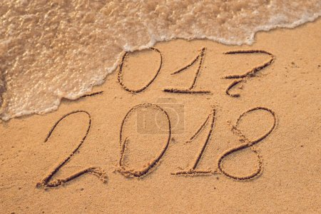 New Year 2018 is coming concept - inscription 2017 and 2018 on a beach sand, the wave is almost covering the digits 2017.