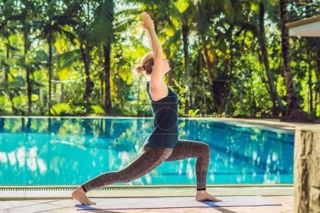 Beautiful young happy woman doing yoga exercise near swimming pool. Healthy lifestyle and good wellness concepts.