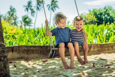 Two little blonde boys having fun on the swing on the tropical sandy coast.