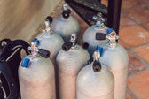 Collection of grey scuba diving air oxygen tanks waiting.