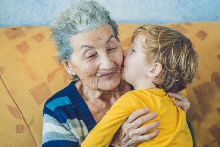 portrait of a Happy boy kissing happy grandmother at home