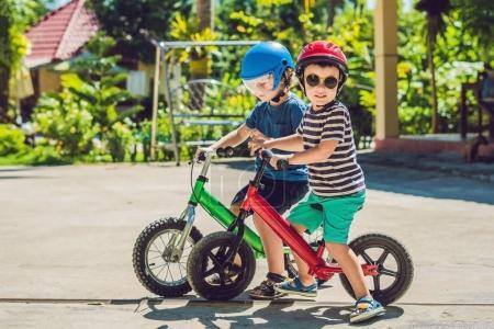 Foto de Dos niños chicos divirtiéndose en la bici del Balance en un camino de país tropical. - Imagen libre de derechos