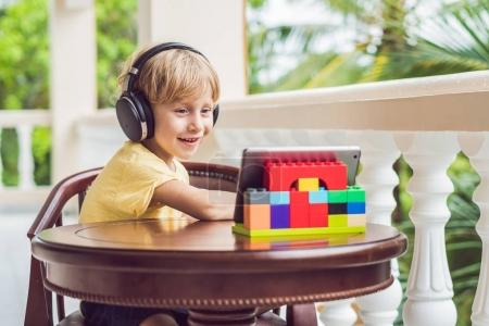 cute boy in the tropics talking with friends and family on video call using a tablet and wireless headphones sitting on the terrace.