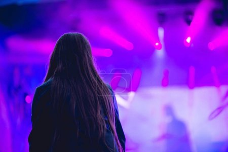 Silhouette of a big crowd at concert against a brightly lit stage. Night time rock concert with people having fun lifting hands up in the air and cheering the musicians.