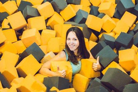 Jeune femme jouant avec des blocs de douces à l'aire de jeux couverte dans la fosse du caoutchouc mousse dans le centre du trampoline