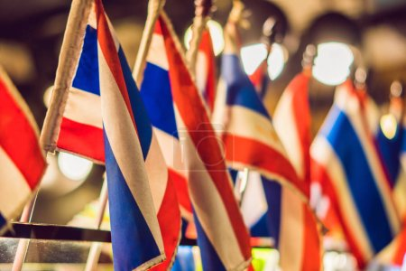 ten small Thai flags indoors on the background of bokeh lights.