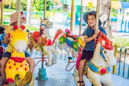 Cute little boy and girl enjoying in funfair and riding on colorful carousel house.