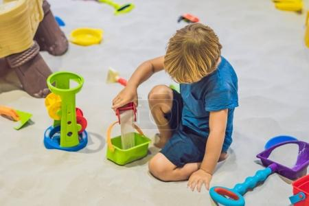 Boy playing with sand in preschool. The development of fine motor concept. Creativity Game concept.