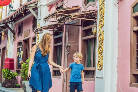 Mother and son walking on Street in Portugese style Romani in Phuket Town. Also called Chinatown or old town. Traveling with children concept