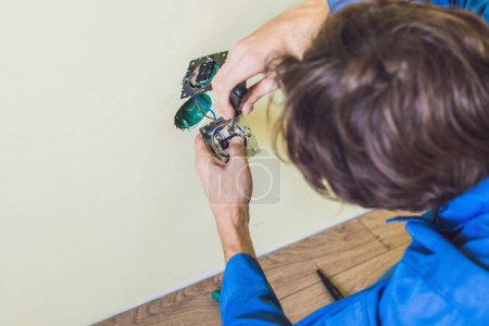 Electrician Installing Socket In New House. Electrician in the house