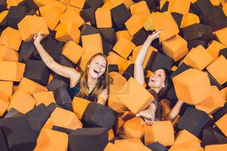 Foto de Dos mujeres jóvenes divertirse con bloques suaves en el interior infantil en centro de trampolín. - Imagen libre de derechos