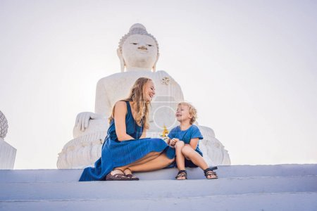 Mother and son tourists on the Big Buddha statue. Was built on a high hilltop of Phuket Thailand Can be seen from a distance. Traveling with children concept.