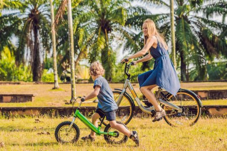 Mother and son riding bikes outdoors and smiling