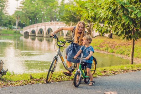 Mother and son riding bikes outdoors and smiling near bridge