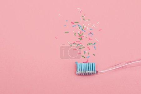 Photo pour Brosse à dents bleue sur fond rose avec saupoudrer. style de mode plat pastel minimal . - image libre de droit