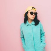 Girl in mint coat and baseball cap