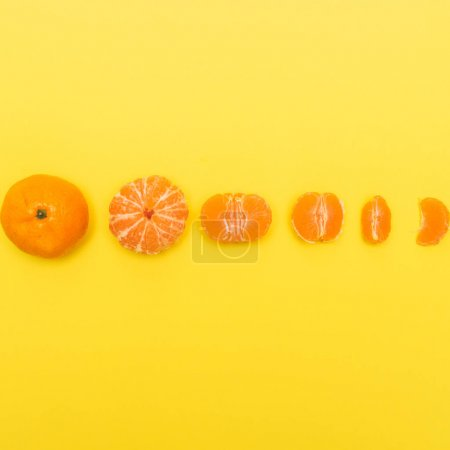 Photo pour Gradual peeling of tangerine on yellow background. - image libre de droit