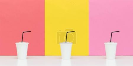 Photo for Three white paper cups with drinking straws on different background - Royalty Free Image