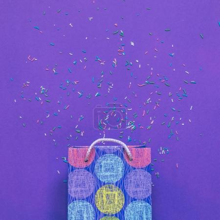 Christmas gift or bag on ultra viotel background with confetti. flat lay, top view. minimalist