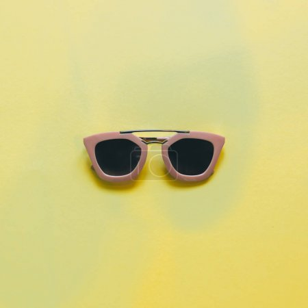 pink sunglasses for woman on yellow background. flat lay. minimal.