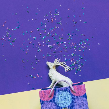 Christmas gift bag and white deer on ultra violet background with confetti.