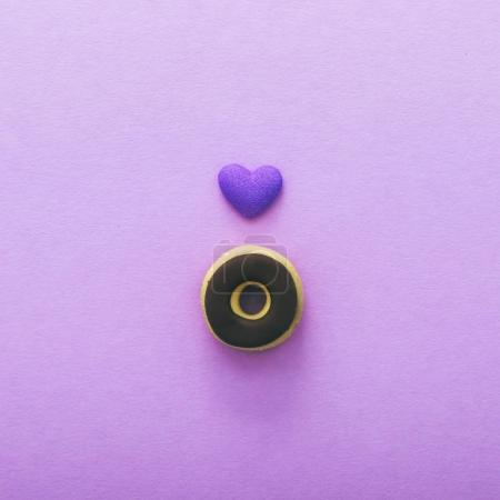 miniature chocolate donut and heart on purple background