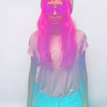 girl in pink wig and sunglasses posing on white background