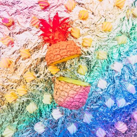 Two painted halves of pineapple with marshmallow on metal foil in vibrant gradient rainbow colors.