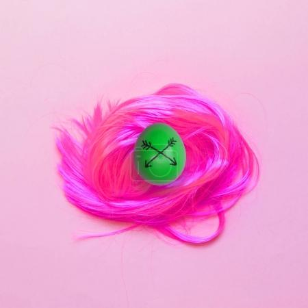 Painted green agg on pink wig. Fahion food art collage. Minimalism