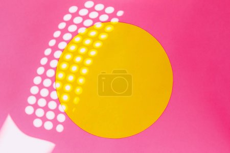 sunbeams reflected on bright pink wall with yellow circle. minimal and surreal creative concept