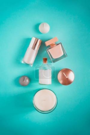 Foto de Spa flatlay de productos de belleza en forma de árbol de Navidad sobre fondo de color turquesa. Aceite de coco, crema de lujo, suero, perfume, velas. - Imagen libre de derechos