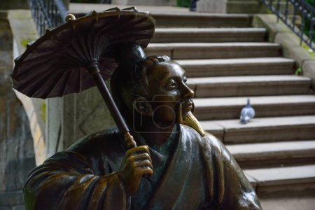 """Bronze sculpture of Chinese with umbrella near the """"Chinese Brid"""