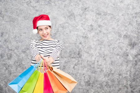 Photo pour Belle jeune fille portant un chapeau de Père Noël tenant beaucoup de sacs à provisions dans la saison des fêtes - image libre de droit