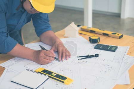 Photo for Architect or planner working on drawings for construction plans at a table - Royalty Free Image