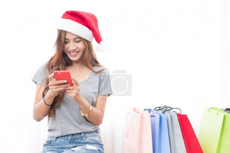 Photo for Beautiful young asian girl wearing a Santa hat with lots of shopping bags in the festive season - Royalty Free Image