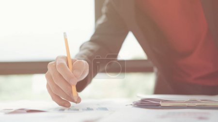 Photo for Young business man holding pen pointing graph data documents working at office, Looking for direction and inspiration - Royalty Free Image
