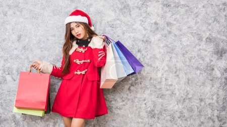 Photo for Beautiful young asian girl wearing a Santa hat holding lots of shopping bags in the festive season - Royalty Free Image