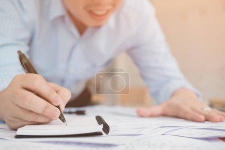 Photo pour Gros plan d'un homme d'affaires tenant un stylo et écrivant ses idées pour de futurs investissements - image libre de droit