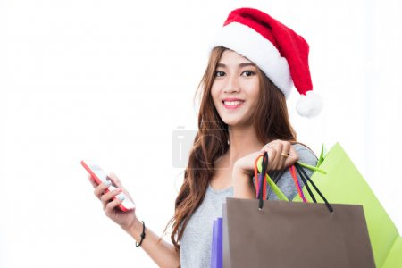 Photo for Beautiful young girl wearing a Santa hat holding lots of shopping bags in the festive season - Royalty Free Image