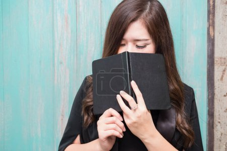 Photo for Closeup on a young asian woman holding a bible and pray, believe concept - Royalty Free Image