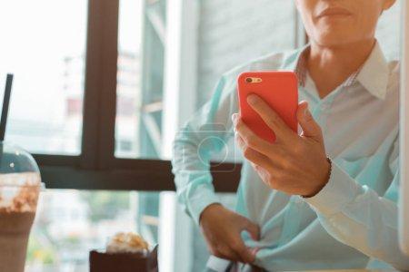 Photo pour Jeune homme d'affaires travaillant dans un café vérifiant son téléphone pour toute communication nécessaire dans des SMS, des appels ou des e-mails - image libre de droit