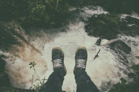 Photo for A man watching the waterfall alone. Looking down on feet, selective focus - Royalty Free Image