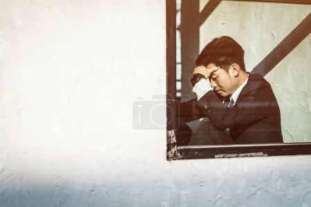 Photo pour Un homme d'affaires stressé se tient la tête dans le désespoir alors qu'il craint de devoir déclarer faillite ou de se mettre en liquidation - image libre de droit
