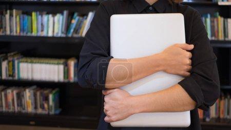Photo pour Bras croisés embrassant un ordinateur, quelqu'un qui aime son travail - image libre de droit