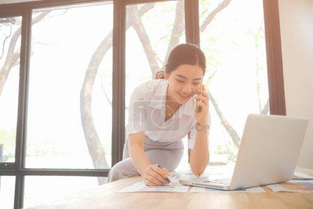 Foto de Joven mujer asiática trabajando en un escritorio en el sector empresarial - Imagen libre de derechos